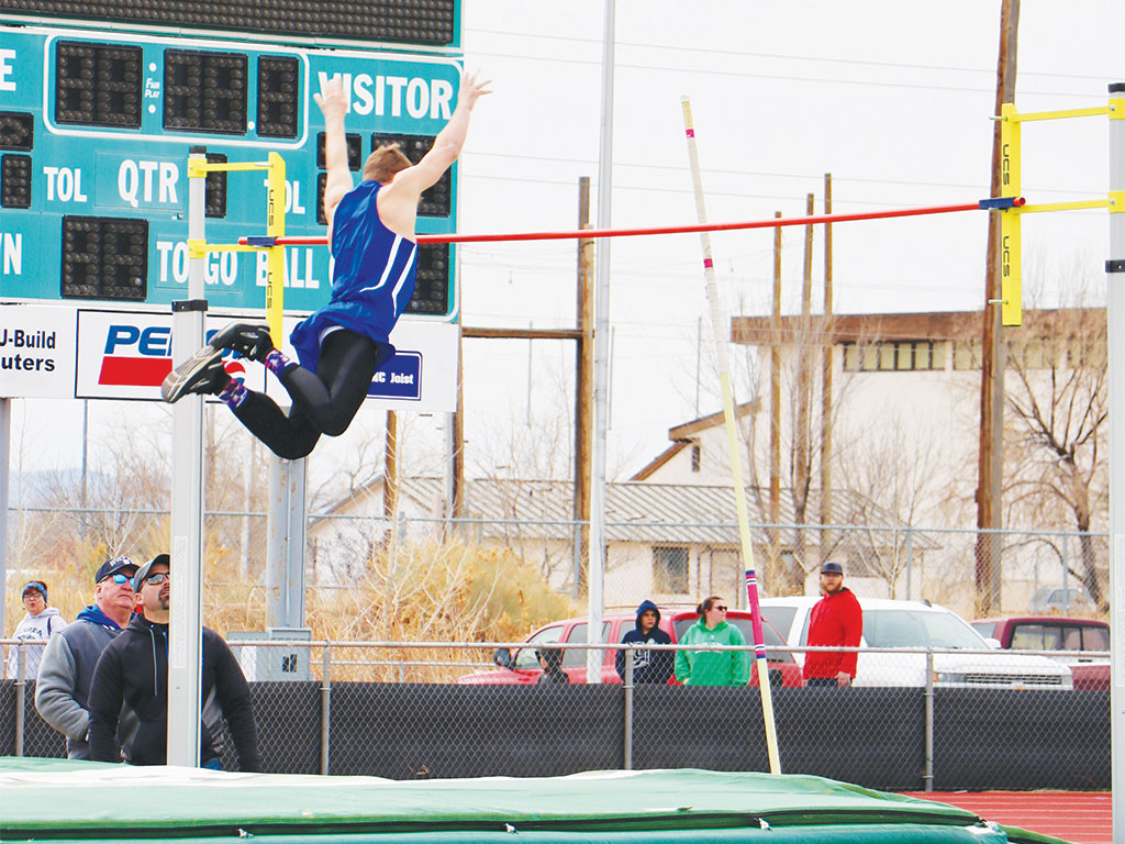 Bryan Day throws his arms up as he clears the bar in pole vault.