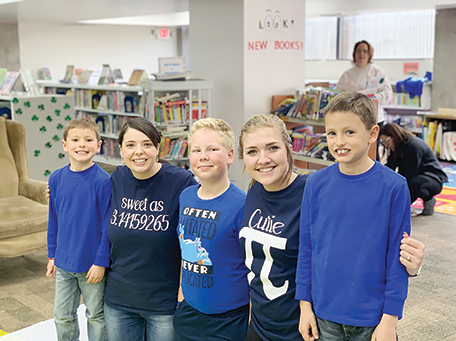 (left to right) Seth Rhodes, age 6, children's librarian Jayme Wells, Andrew Egbert, age 9, children's librarian Jasmine Marchand and Shane Rhodes, age 9 stop for a photo before the kids get to pie the librarians in the face.