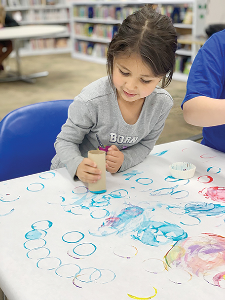 Emma Castaneda, age 5, uses an empty toilet paper roll and paint to make circles on paper in celebration of pi day.
