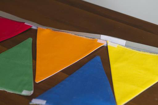 Create a template for the pennants out of cardboard or cardstock by drawing a triangle that measures 6 1/2 inches across the base and 6 1/2 inches tall.